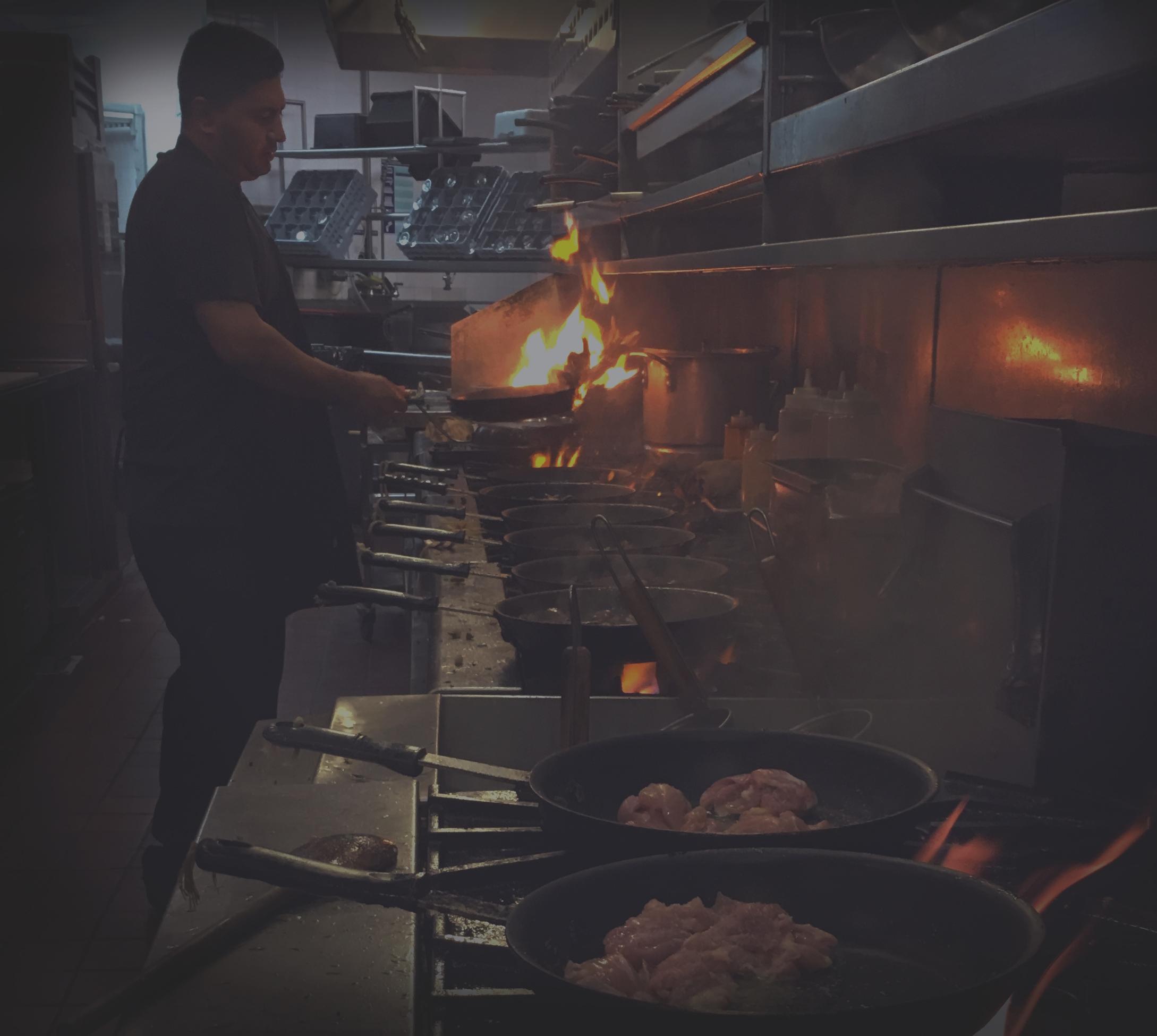 El Pollo Inka chef frying food on range